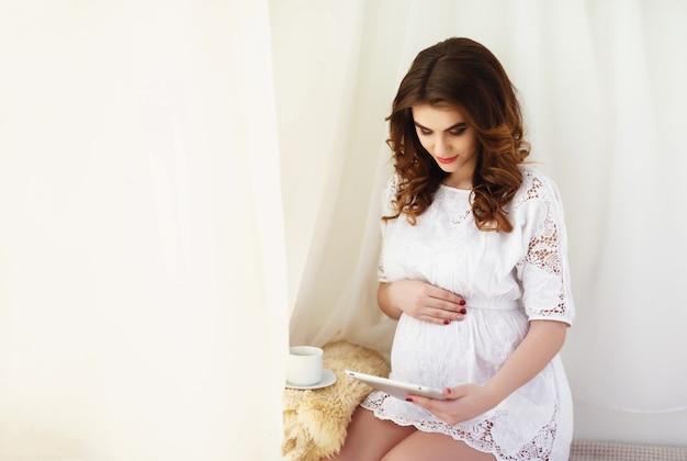 Belle femme enceinte utilise une tablette numérique tout en restant assis sur le canapé à la maison