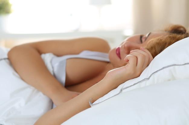 Belle femme endormie dans sa chambre le matin. concentrez-vous à portée de main. copyspace.