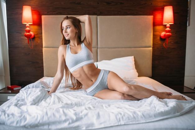 Belle femme endormie réveillée dans le lit