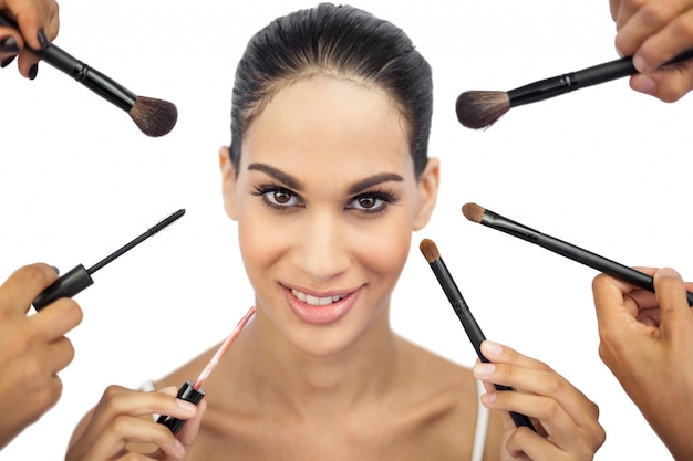Belle femme entourée de pinceaux de maquillage