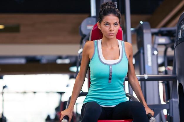 Belle femme d'entraînement sur la machine d'exercices dans la salle de fitness