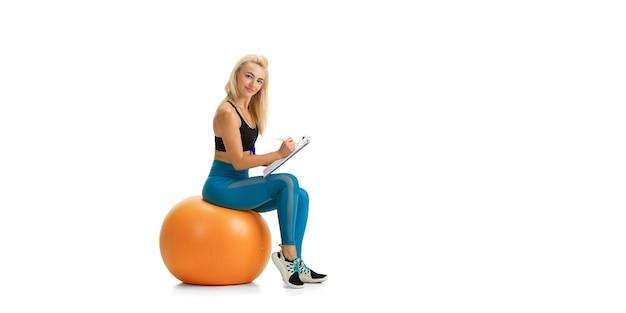 Belle femme entraîneur de fitness pratiquant isolé sur mur blanc