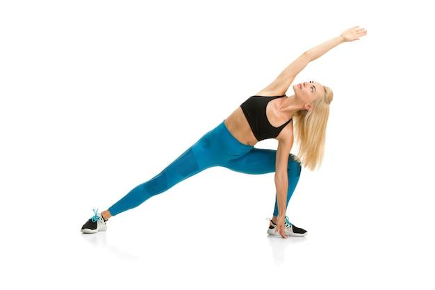 Belle femme entraîneur de fitness pratiquant isolé sur mur de studio blanc