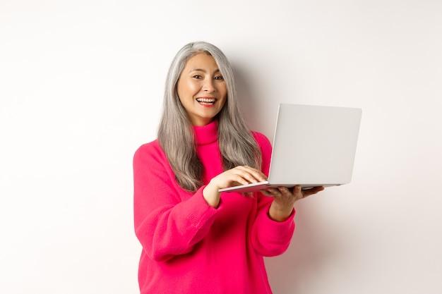 Belle femme entrepreneur asiatique senior travaillant avec un ordinateur portable en riant et souriant à la caméra debout...