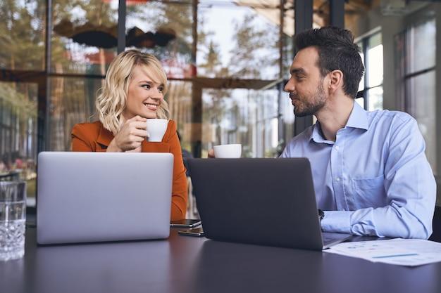 Belle femme entrepreneur caucasienne joyeuse avec une tasse souriant à son jeune collègue masculin aux cheveux noirs