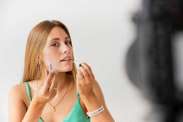 Belle femme essayant de brillant à lèvres