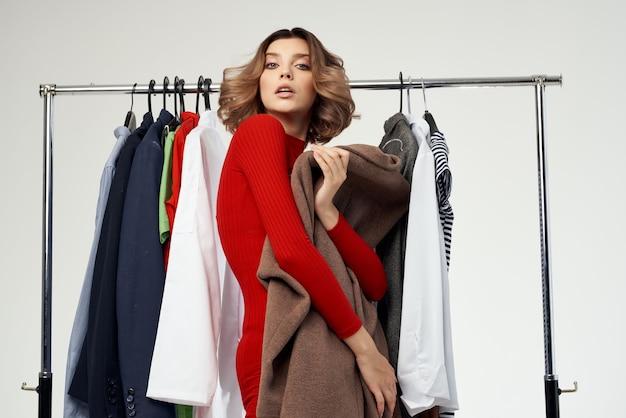 Belle femme essayant sur fond clair accro du shopping magasin de vêtements