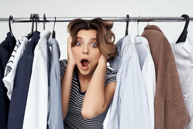 Belle femme essayant sur fond clair de magasin de vêtements au détail