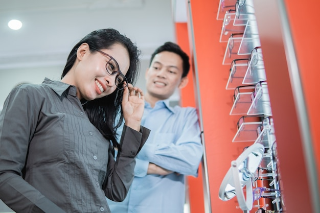 Une belle femme essayant de porter des lunettes et de refléter une serveuse de magasin