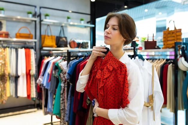 Belle femme essayer une robe rouge et penser dans un grand centre commercial
