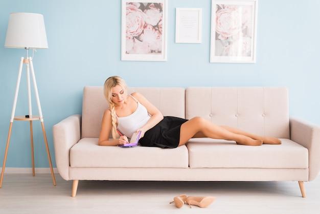 Une belle femme est allongée sur le canapé avec un bloc-notes