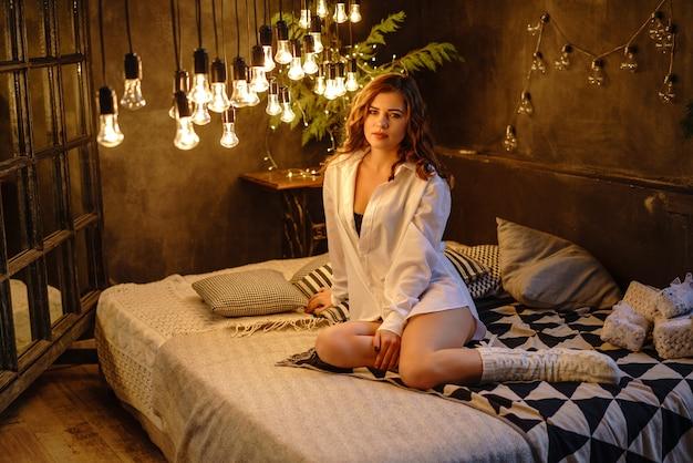 Une belle femme est allongée sur un lit en chemise blanche. brille magnifiquement les ampoules.