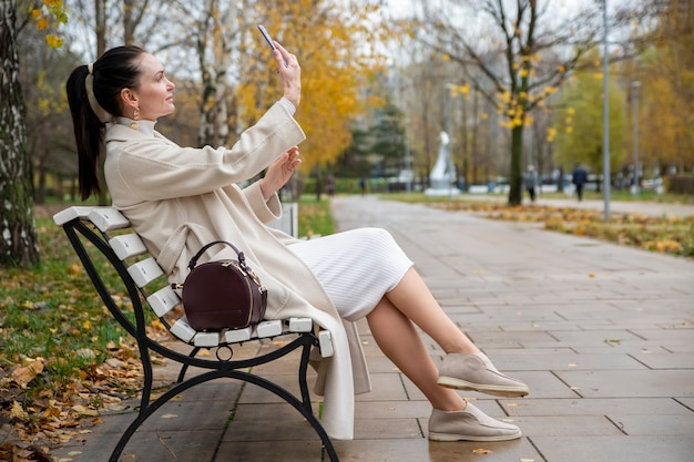 Belle femme est assise sur un banc dans le parc... femme d'âge moyen prenant un selfie au téléphone dans le parc