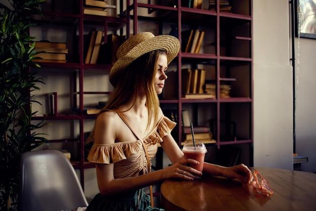 Belle femme est assise à une table dans un verre de café de jus de détente plus amusant. photo de haute qualité
