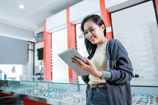 Une belle femme est dans une clinique ophtalmologique et regarde une liste de produits de lunettes avec un fond de fenêtre d'affichage de lunettes