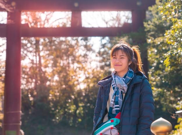 Belle femme est portrait en vêtements d'hiver dans le sanctuaire du temple japonais