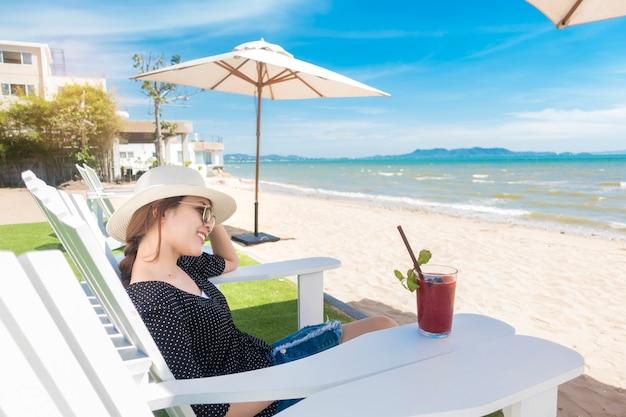Belle femme est relaxante sur la plage, sous un parasol