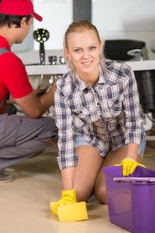 Belle femme est en train de nettoyer le sol dans la salle de bain.