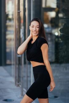 Belle femme, été en ville, entraînement de fitness dans la rue, vêtements de sport.