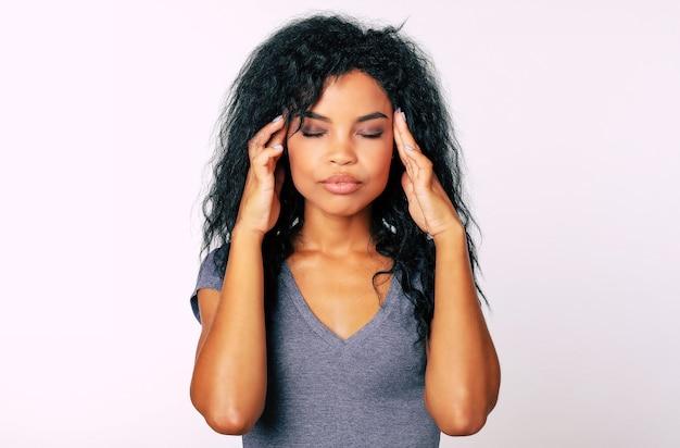 Belle femme ethnique africaine en t-shirt gris se tient face à la caméra, les yeux fermés et les doigts touchant les tempes en signe de stress ou de maux de tête
