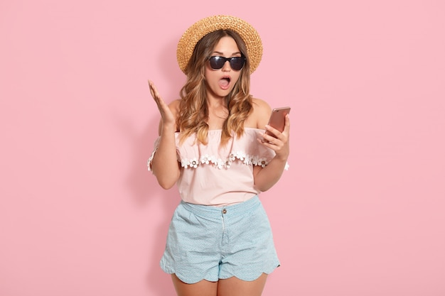 Belle femme étonnée portant un chemisier avec des épaules dénudées, un chapeau court en paille et des lunettes de soleil, tenant le téléphone intelligent à la main et posant avec la bouche ouverte, reçoit des messages choquants d'un ami.