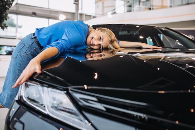 Belle femme étreignant une voiture dans un showrrom de voiture