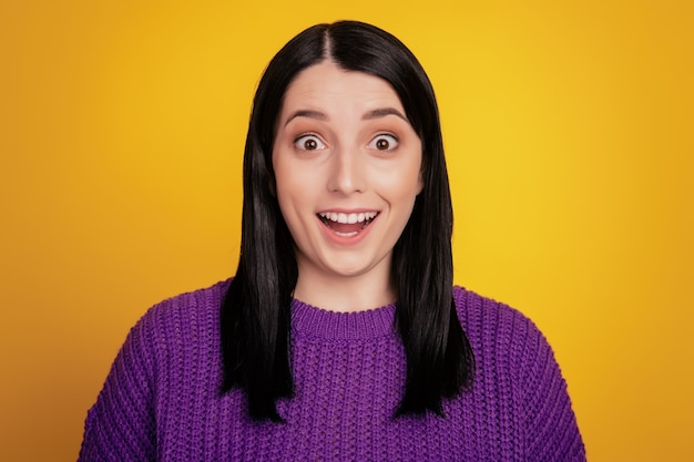 Une belle femme excitée ne s'attend pas à recevoir une agréable surprise d'un ami proche choqué isolé sur fond jaune