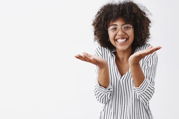 Belle femme expliquant quelque chose de simple en haussant les épaules et en levant les paumes dans une expression ignorante et inconsciente souriant largement de rire de plaisir et de joie