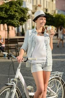 Belle femme, faire du vélo dans la rue en ville.