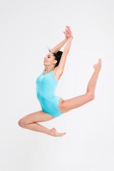 Belle femme faisant acrobatique stunt isolé sur un mur blanc