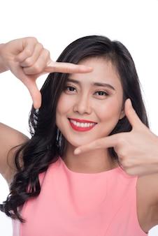 Belle femme faisant un cadre avec les doigts devant le visage