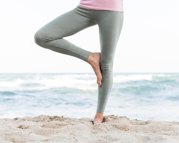 Belle femme faisant du yoga à la plage