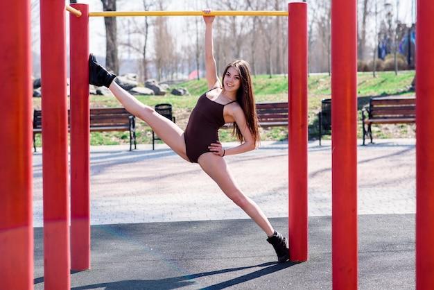Belle femme faisant des étirements sur un terrain de sport
