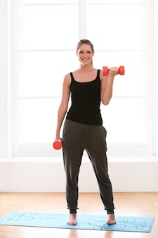 Belle femme faisant des exercices de fitness à la maison