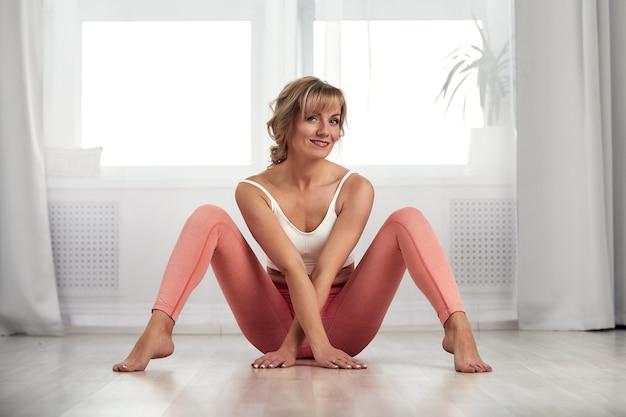 Belle femme faisant des exercices à la maison dans un salon