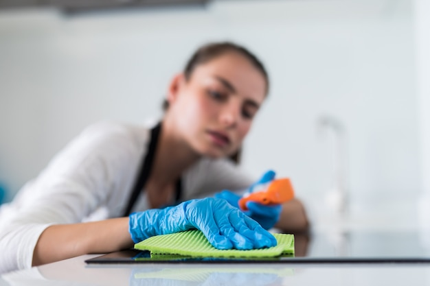 Belle femme faisant le ménage tout en nettoyant dans la cuisine