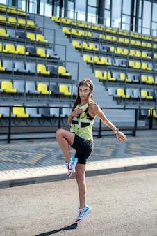 Belle femme faisant des poses de yoga sur un stade de la ville. concept de mode de vie sain