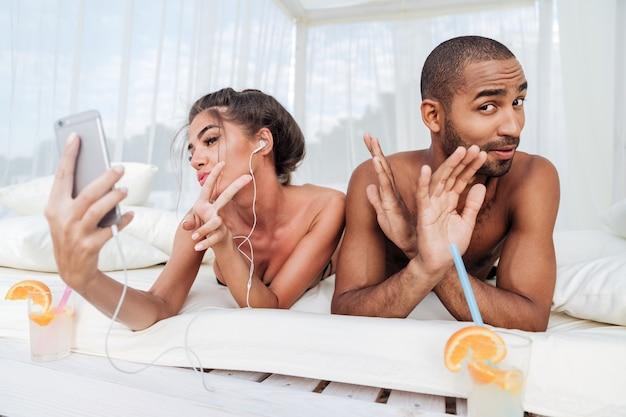 Belle femme faisant selfie avec smartphone et montrant le signe v avec bel homme africain à la plage
