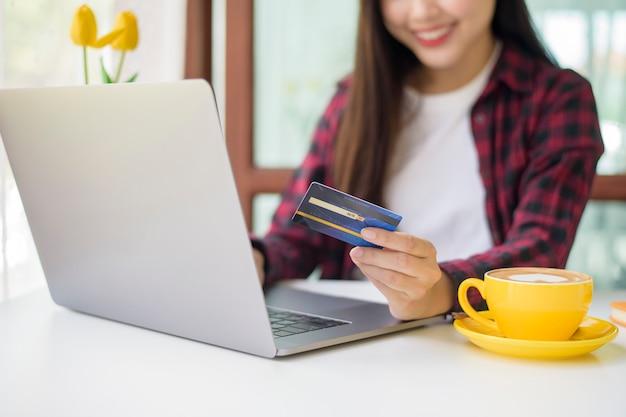 Belle femme fait des achats en ligne avec carte de crédit dans un café