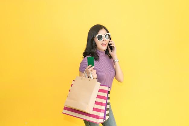 Belle femme fait du shopping dans le centre commercial en utilisant la carte de crédit. femme portant des lunettes et tenant la mode sac à provisions dans le magasin.