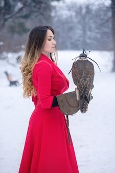 Belle femme et faucon en hiver