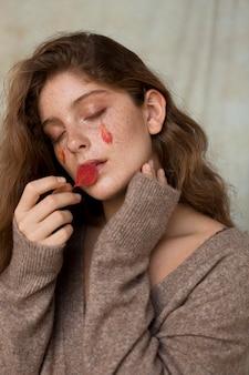 Belle femme avec des feuilles sur son visage et ses lèvres