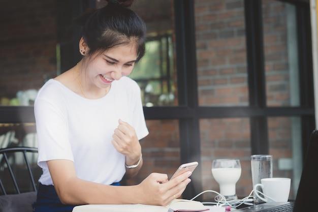 Belle femme, fille à l'aide de téléphone portable avec plaisir et heureux dans le temps libre dans un café.
