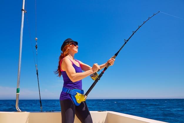 Belle femme fille canne à pêche à la traîne en bateau