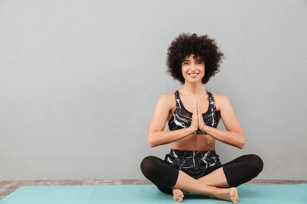 Belle femme fitness bouclée faire des exercices de yoga sport