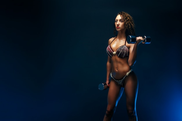 Belle femme fitness soulevant des haltères.