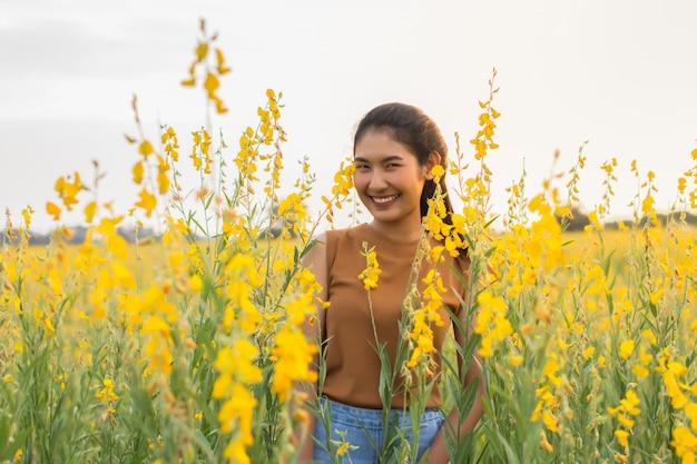 Belle femme avec fleur crotalaria pendant la soirée