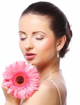 Belle femme avec une fleur rose isolée on white