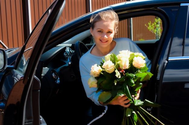 Belle femme avec des fleurs dans une voiture chère.
