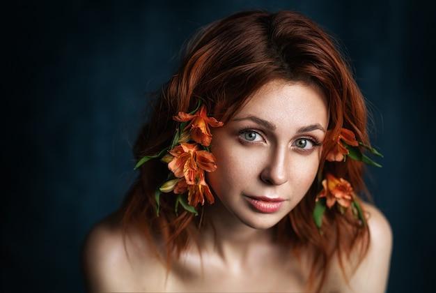 Belle femme avec des fleurs. gros plan du visage. maquillage et coiffure